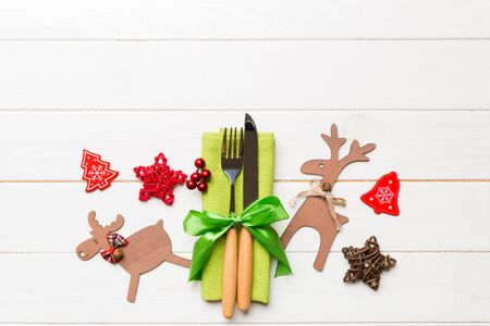 Top view of new year utensils on napkin with holiday decorations and reindeer on wooden background. Christmas dinner concept with copy space.