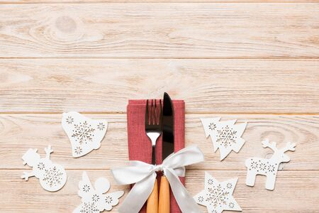 Top view of New Year dinner on wooden background. Festive cutlery on napkin with christmas decorations and toys. Family holiday concept with copy space. Stock Photo