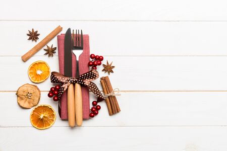 Top view of utensils on festive napkin on wooden background. Christmas decorations with dried fruits and cinnamon. New year dinner concept with copy space.
