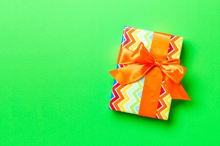 Top view Christmas present box with orange bow on green background with copy space. Stockfoto