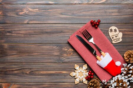 Top view of fork and knife on napkin on wooden background. Different christmas decorations and toys. New Year dinner concept with empty space for your design.