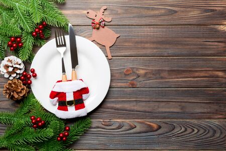 Top view of Christmas dinner on wooden background. Plate, utensil, fir tree and holiday decorations with copy space. New Year time concept. Stock Photo