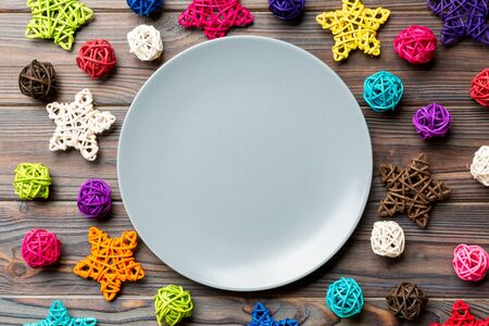 Top view of holiday plate decorated with knitted baubles and stars on wooden background. New Year decorations and toys. Family Christmas dinner concept. 스톡 콘텐츠