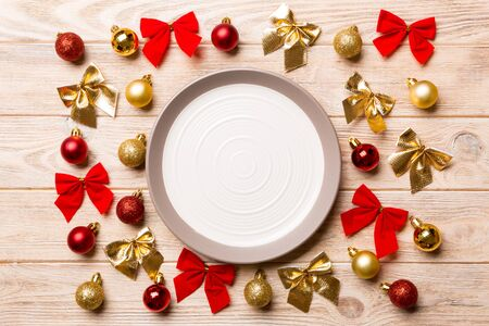 Top view of holiday dinner on wooden background. Plate, baubles and bows. Christmas Eve concept. Stock fotó
