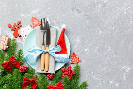 Top view of Christmas dinner on cement background. Plate, utensil, fir tree and holiday decorations with copy space. New Year time concept. Stock Photo