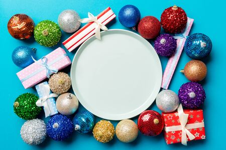Top view of holiday setting on colorful background. Plate, gifts, baubles and Christmas decorations. New Year dinner concept.