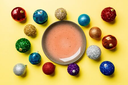 Top view of empty plate surrounded with colorful baubles on yellow background. New Year decorations. Christmas Eve concept. Stock fotó