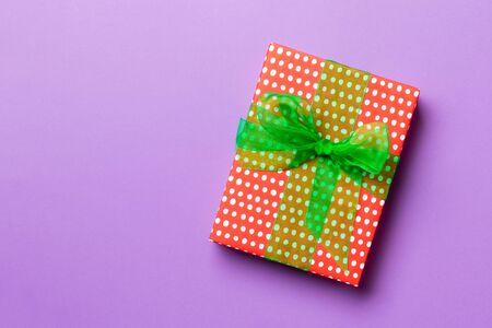 wrapped Christmas or other holiday handmade present in paper with green ribbon on purple background. Present box, decoration of gift on colored table, top view with copy space.