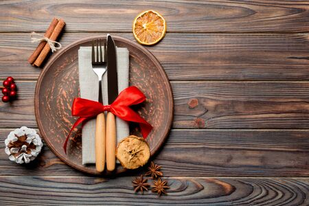 Top view of holiday dinner decorated with dried fruit and cinnamon on wooden background. Set of plate, urensil and New Year decorations. Christmas time concept with epmty space for your design.