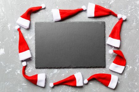 Festive set of plate decorated with Santa Claus hat on cement background. Top view christmas dinner concept. Stock fotó