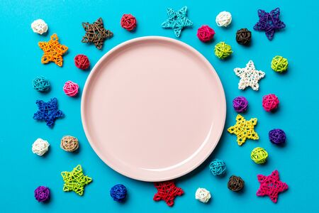 Top view of holiday plate decorated with knitted baubles and stars on colorful background. New Year decorations and toys. Family Christmas dinner concept. Stock fotó