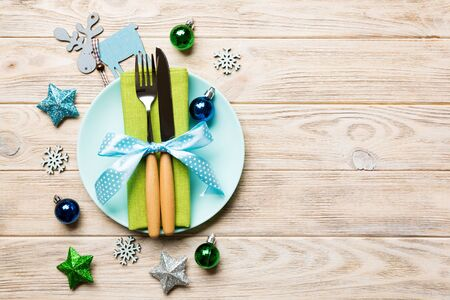 Holiday composition of Christmas dinner on wooden background. Top view of plate, utensil and festive decorations. New Year Advent concept with copy space. Stock fotó