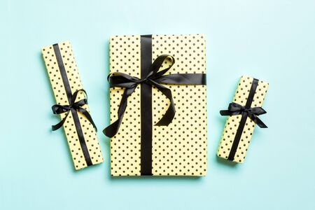 wrapped Christmas or other holiday handmade present in paper with Black ribbon on blue background. Present box, decoration of gift on colored table, top view. Stok Fotoğraf