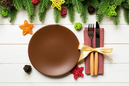 Top view of New Year dinner on festive wooden background. Composition of plate, fork, knife, fir tree and decorations. Merry Christmas concept.