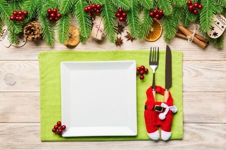 Top view of Christmas dinner on wooden background. Plate, utensil, fir tree and holiday decorations with copy space. New Year time concept. Stock fotó