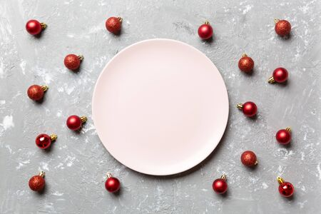 Top view of festive plate with red baubles on cement background. Christmas decorations and toys. New Year advent concept. Stock fotó