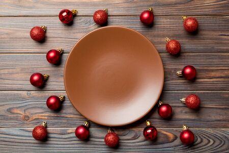 Top view of festive plate with red baubles on wooden background. Christmas decorations and toys. New Year advent concept. Stock fotó
