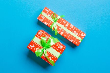 wrapped Christmas or other holiday handmade present in paper with green ribbon on blue background. Present box, decoration of gift on colored table, top view.