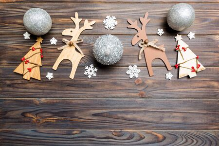 New Year composition made of baubles, reindeer and other decorations on wooden background. Christmas time concept with empty space for your design.