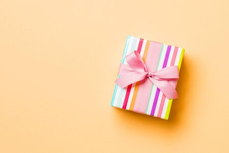 Top view Christmas present box with pink bow on orange background with copy space. Stock fotó