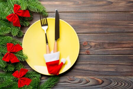 Holiday composition of plate and flatware decorated with Santa hat on wooden background. Top view of Christmas decorations with empty space for your design. Festive time concept.