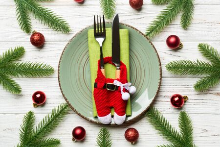 Top view of fork, knife and plate surrounded with fir tree and Christmas decoratoins on wooden background. New Year Eve and holiday dinner concept. 스톡 콘텐츠