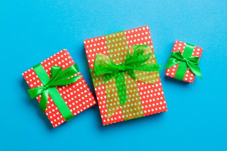 Gift box with green bow for Christmas or New Year day on blue background, top view.
