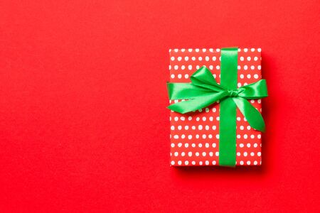 Top view Christmas present box with green bow on red background with copy space. 스톡 콘텐츠