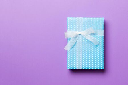 wrapped Christmas or other holiday handmade present in paper with white ribbon on purple background. Present box, decoration of gift on colored table, top view with copy space.