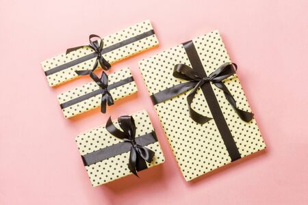 Top view Christmas present box with Black bow on pink background. 스톡 콘텐츠