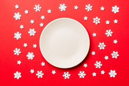 Top view of empty plate surrounded with snowflakes on colorful background. New Year dinner concept.