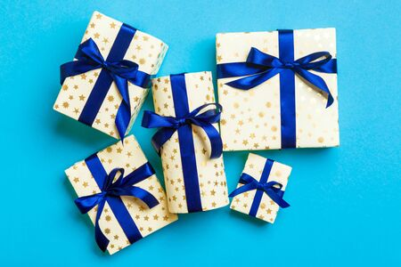 wrapped Christmas or other holiday handmade present in paper with blue ribbon on blue background. Present box, decoration of gift on colored table, top view.