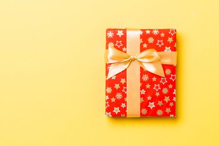 Top view Christmas present box with gold bow on yellow background with copy space.