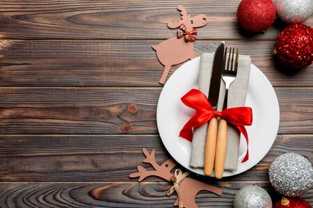 Holiday composition of Christmas dinner on wooden background. Top view of plate, utensil and festive decorations. New Year Advent concept with copy space. 스톡 콘텐츠