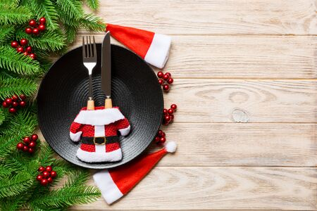 Holiday composition of plate and flatware decorated with Santa hat and clothes on wooden background. Top view of Christmas decorations with empty space for your design. Festive time concept.