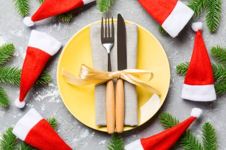 Holiday composition of plate and flatware decorated with Santa hat on cement background. Top view of Christmas decorations. Festive time concept.