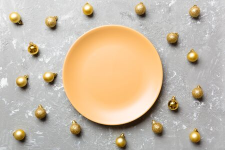 Top view of festive plate with golden baubles on cement background. Christmas decorations and toys. New Year advent concept. 스톡 콘텐츠