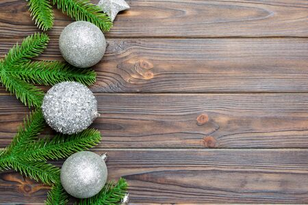 Set of festive balls, fir tree and Christmas decorations on wooden background. Top view of New Year ornament concept with copy space.