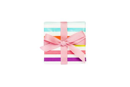 Christmas or other holiday handmade present in colored paper with pink ribbon. Isolated on white background, top view. thanksgiving Gift box concept.