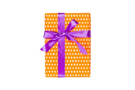 Christmas or other holiday handmade present in orange paper with purple ribbon. Isolated on white background, top view. thanksgiving Gift box concept.
