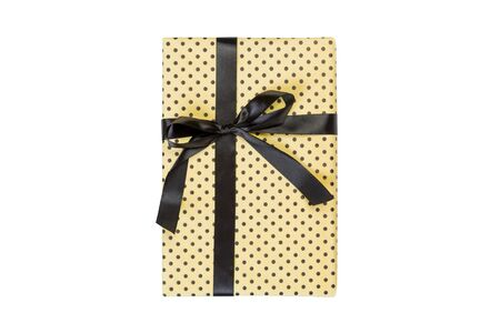 Christmas or other holiday handmade present in yellow paper with black ribbon. Isolated on white background, top view. thanksgiving Gift box concept.