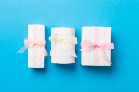 Gift box with Colored bow for Christmas or New Year day on blue background, top view.