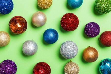 Top view of creative holiday baubles on colorful background. Christmas ornament concept.