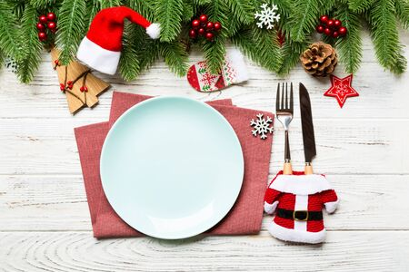 Top view of Christmas dinner on wooden background. Plate, utensil, fir tree and holiday decorations with copy space. New Year time concept. 스톡 콘텐츠