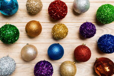 Top view of creative holiday baubles on wooden background. Christmas ornament concept.