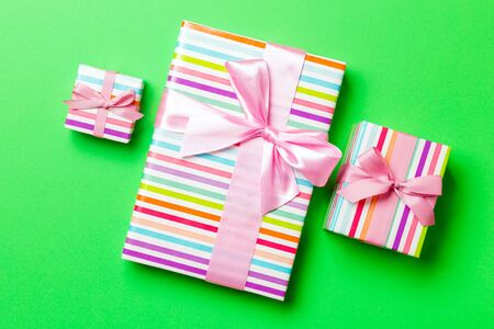 Top view Christmas present box with pink bow on green background. 스톡 콘텐츠