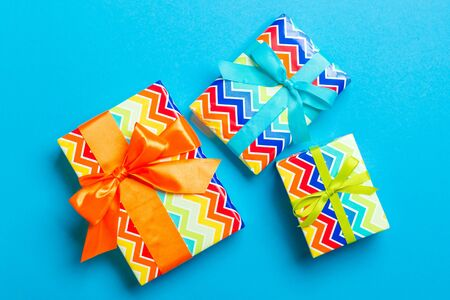 wrapped Christmas or other holiday handmade present in paper with blue, green and orange ribbon on blue background. Present box, decoration of gift on colored table, top view. 스톡 콘텐츠