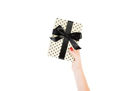 Woman hands give wrapped Christmas or other holiday handmade present in yellow paper with black ribbon. Isolated on white background, top view. thanksgiving Gift box concept.