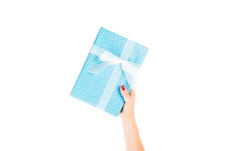 Woman hands give wrapped Christmas or other holiday handmade present in blue paper with white ribbon. Isolated on white background, top view. thanksgiving Gift box concept. 스톡 콘텐츠