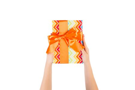 Woman hands give wrapped Christmas or other holiday handmade present in colored paper with orange ribbon. Isolated on white background, top view. thanksgiving Gift box concept. 스톡 콘텐츠